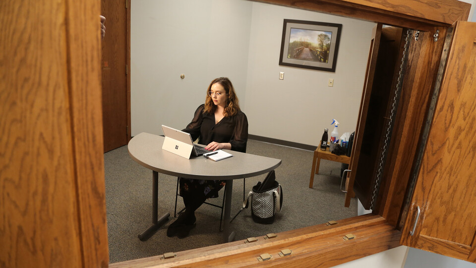 Brenna Lash, a graduate student, loads the Telehealth platform on her laptop computer, as seen from an observation room, where clinic faculty supervisors monitor sessions.