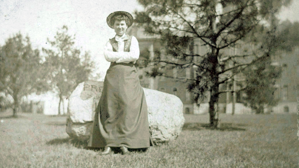 Willa Cather poses in front of a rock while she was on the University of Nebraska campus. The rock is now located in front of Morrill Hall.