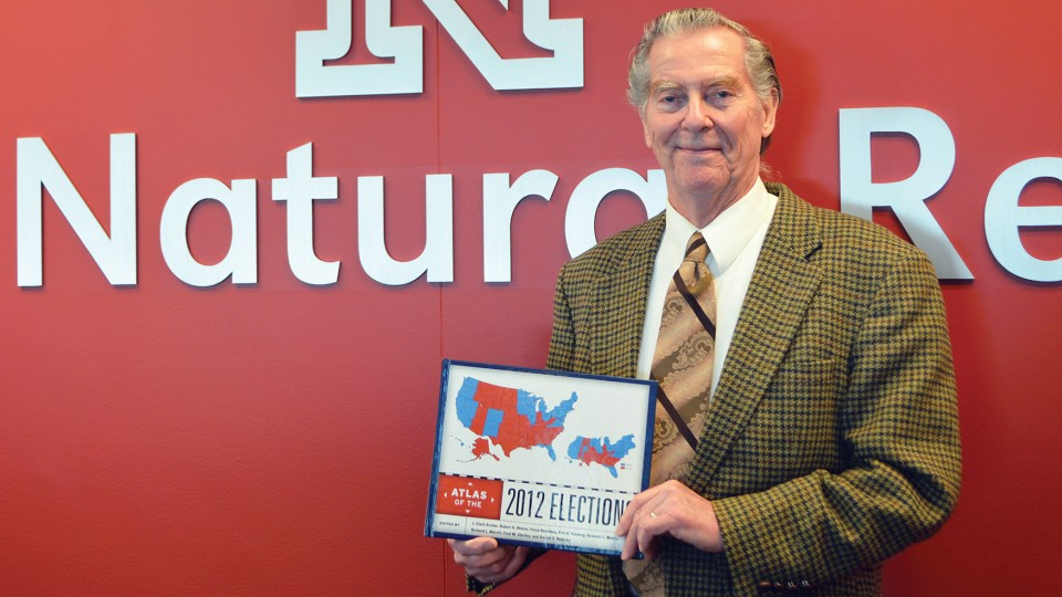 "Clark Archer holds his new book, ""Atlas of the 2012 Elections."""