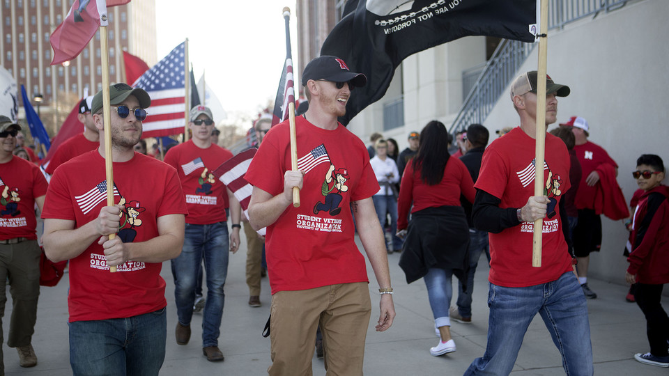 Jake Post (center) and other members of Nebraska's Student Veteran Organization lead the 2017 Things They Carry Ruck March into Memorial Stadium prior to the Huskers-Hawkeyes football game.
