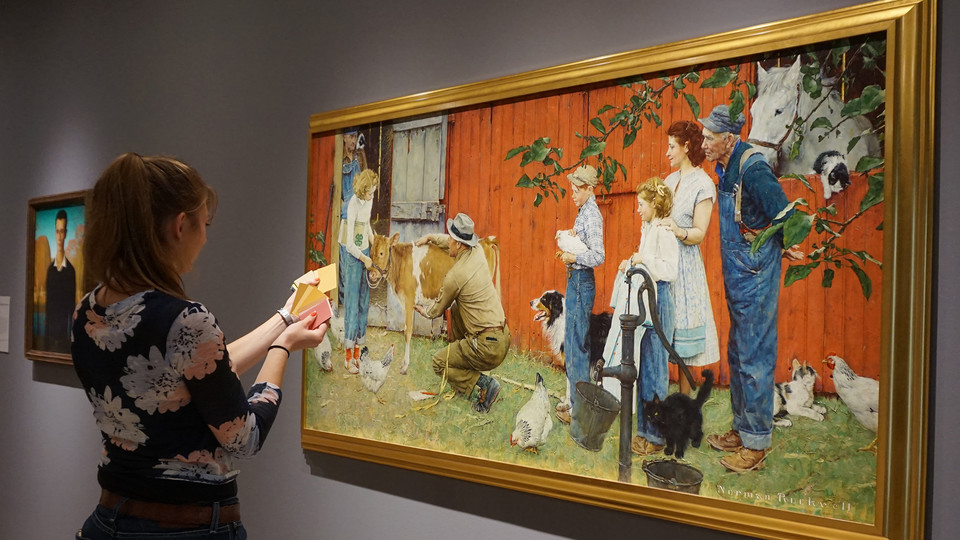 "A Nebraska student uses paint swatches to match colors to Norman Rockwell's ""The County Agricultural Agent"" painting in the Sheldon. The project was part of a Textiles, Merchandising and Fashion Design class project to create a color palette based on a Sheldon artwork."