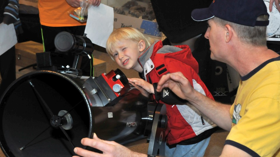 Dan Kincheloe, a member of the Prairie Astronomy Club, helps Benjamin Mount with a telescope during Astronomy Day at Morrill Hall. The museum's Sunday with a Scientist program will feature telescopes and the night sky on Sept. 22.