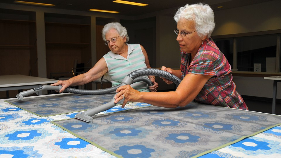 Museum volunteers vacuum dust from a quilt. Screens are used to protect the quilt during the process.