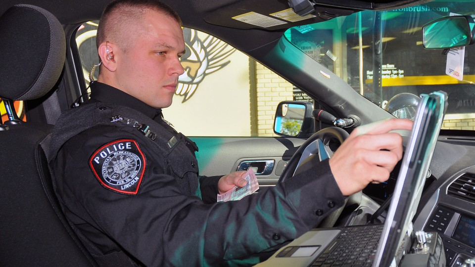 Officer Eric Fischer accesses a driver's information during a stop on Oct. 17. The UNL Police Department is seeking accreditation from the Commission on Accreditation for Law Enforcement Agencies. A final onsite review begins Nov. 9.