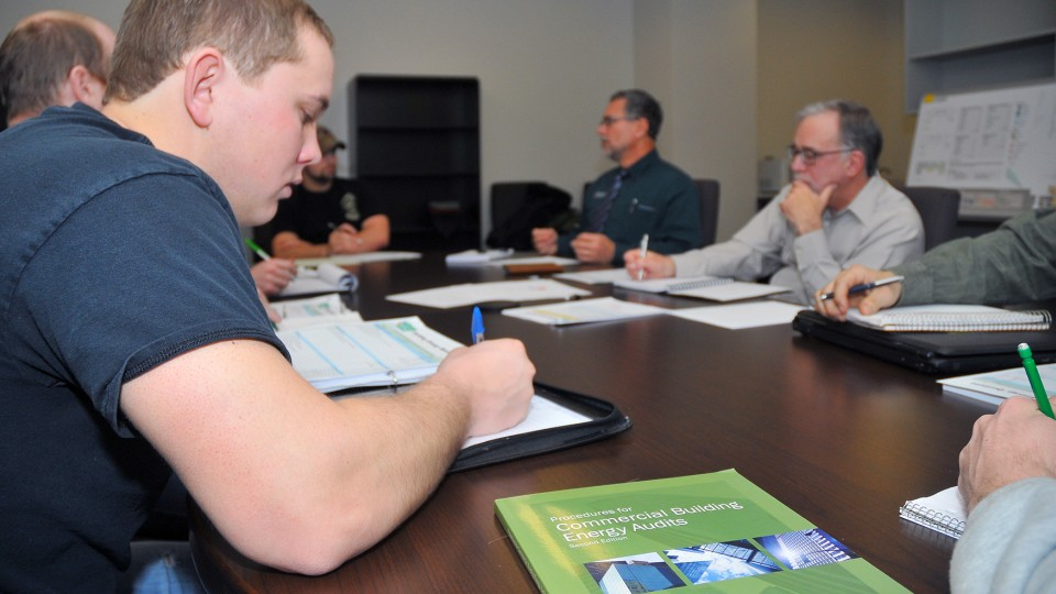 UNL engineering students write down answers during an interview with Kirk Conger. The students are conducting energy audits of UNL buildings as part of a pilot course in engineering.