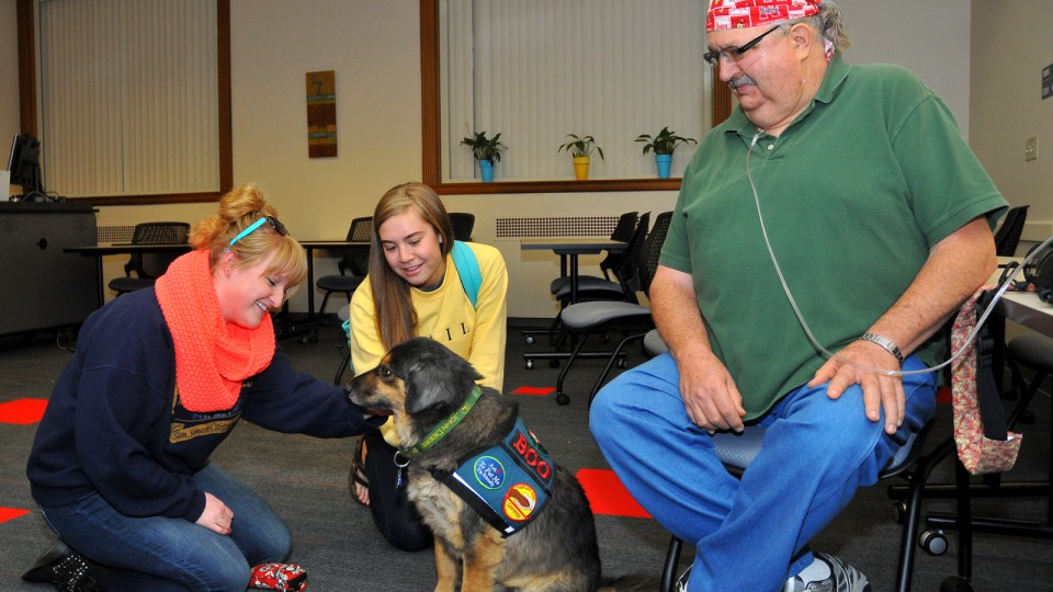 UNL students (from left) Lauren Martin and Laura Kowalski pet Boo, a Healing Hearts Therapy Dog, in Love Library on Oct. 15. Boo is a therapy and service dog owned by Gary Royal (right).