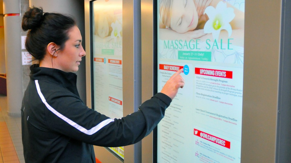 Kaylie Martens, a senior nutrition, exercise and health sciences major, uses the new digital touchscreen in the Campus Rec Center on City Campus. The boards are part of a campuswide initiative.