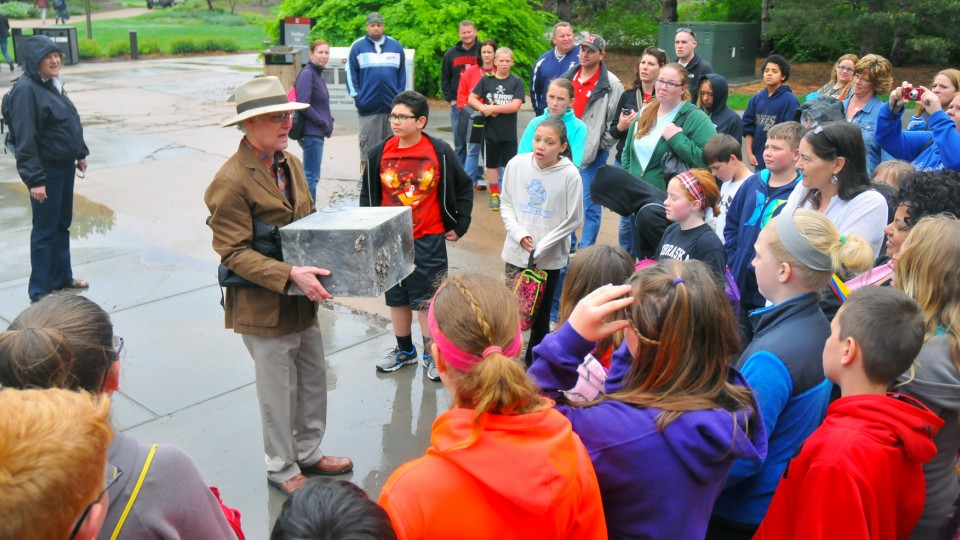 Mark Griep, professor of chemistry, shows the Avery Hall cornerstone time capsule to a group of students from York Middle School. The time capsule was removed on May 12.