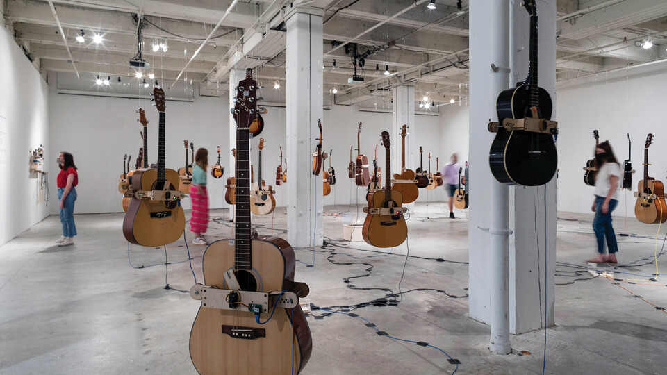 """Guitars hang in the air as patrons examine the """"Soundtracks for the Present Future"""" exhibition in Omaha's Bemis Center for Contemporary Arts."""