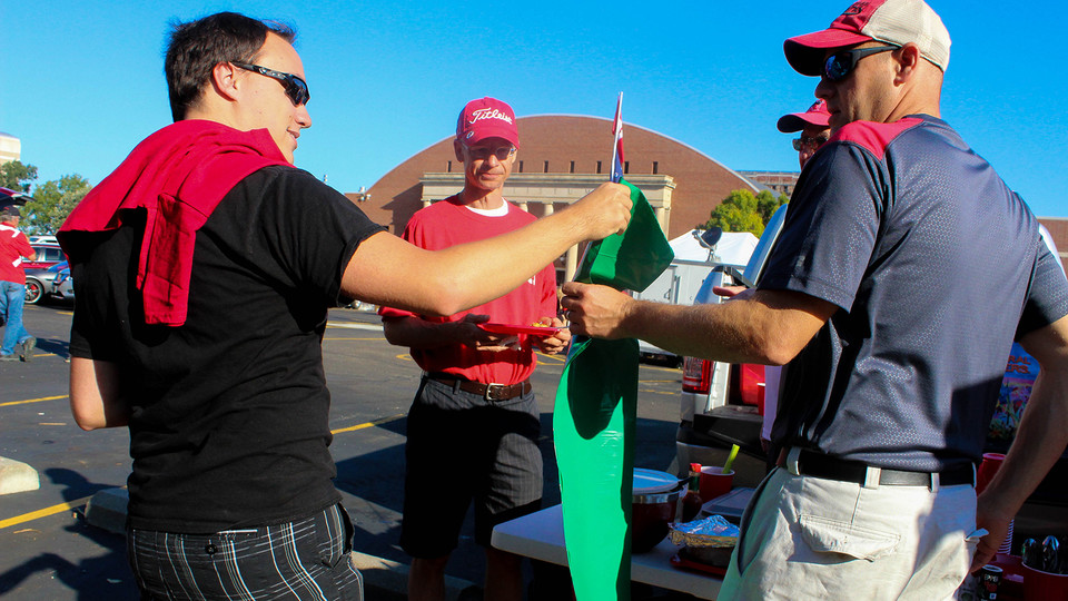 A Go Green for Big Red volunteer (left) hands out a green bag to collect tailgating recyclables during Nebraska's 2018 football season. The recycling program begins its 11th season on Aug. 31.
