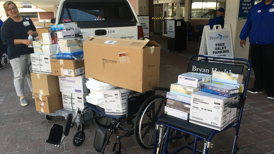 Bryan Health workers load supplies from Jessica Corman's truck into a pair of wheelchairs. The supplies were donated by campus labs.