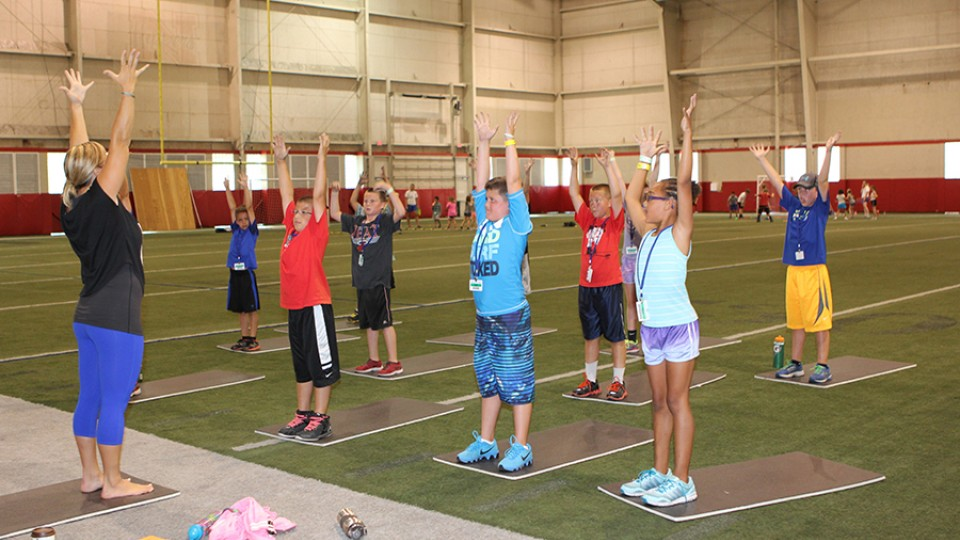 Husker Kids take part in a stretching activity as part of Campus Recreation's summer camp. The program is now in its 25th year, having shown more than 6,920 children the benefit of living an active lifestyle.