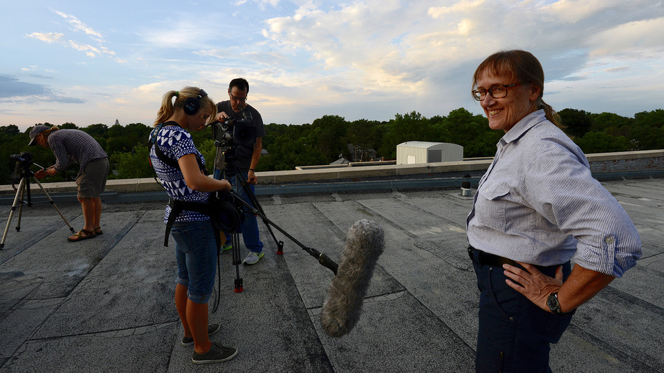 Nebraska's Mary Bomberger Brown (right) smiles as a crew prepares for an interview. Bomberger Brown, a Nebraska graduate and faculty member, dedicated her career to conservation, especially with endangered bird populations.