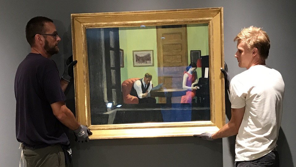 """Sheldon employees install """"Room in New York"""" by Edward Hopper. The iconic artwork is featured in the museum's new exhibition, """"Sheldon Treasures."""""""