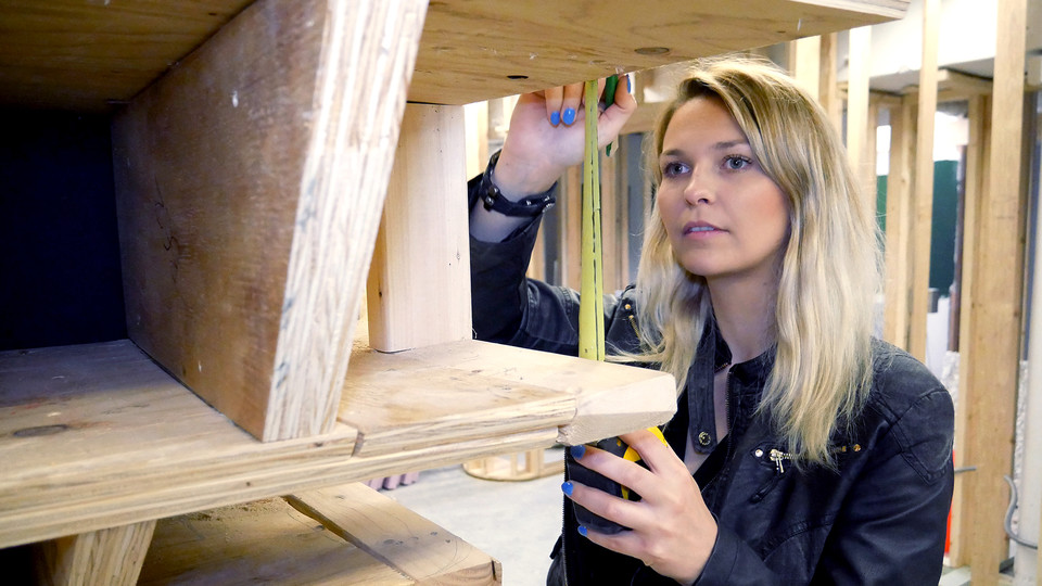 Maren Elnes, a graduate student in architecture, double checks measurements at the new interior facility at Omaha's Bemis Center.