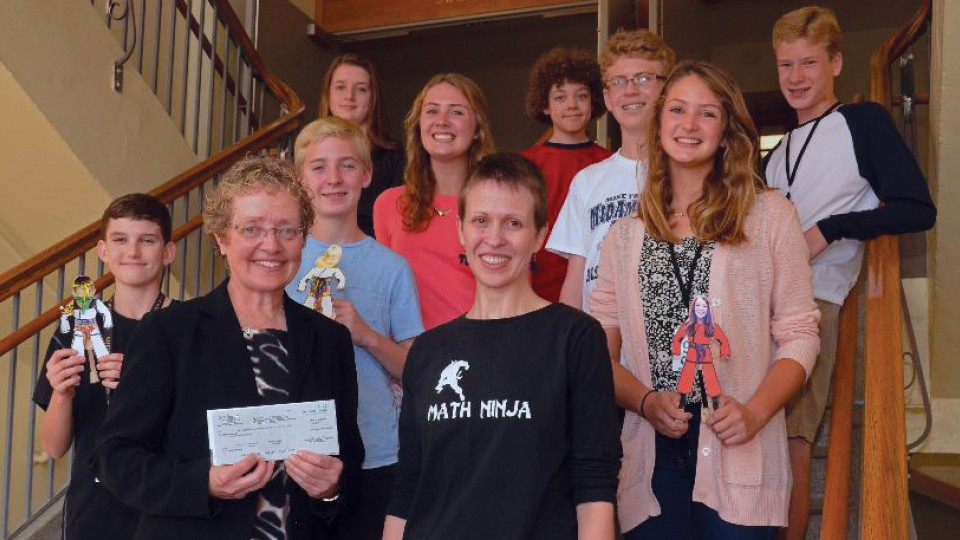 Jocelyn Bosley (front row, second from left) presents a Math Hero award check to members of Irving Middle School. Bosley's 2015 Math Hero award included funds for the institution she worked with on her mentoring project.