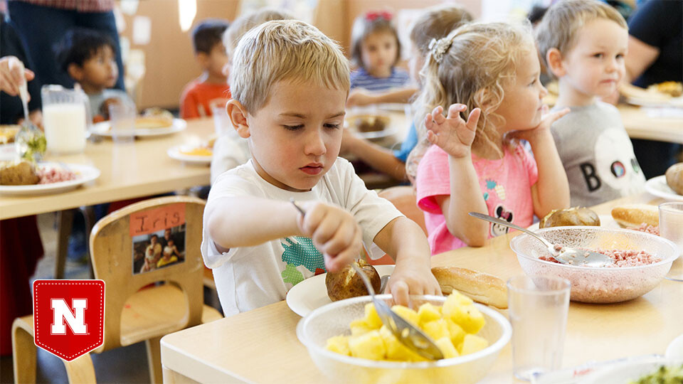 A child takes a helping of pineapple in a child care setting