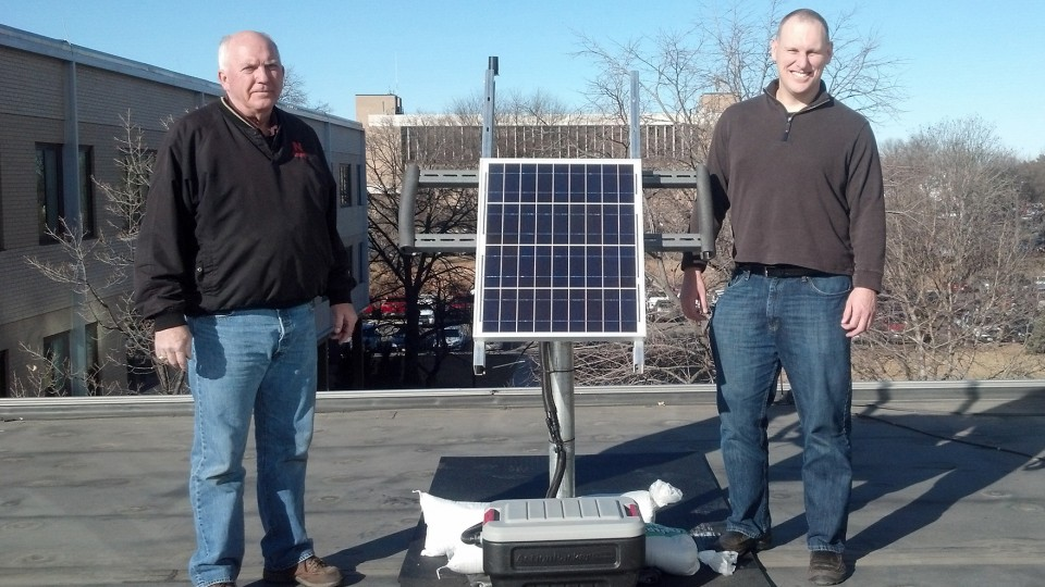 Rick Perk (left), assistant geologist, and Brian Wardlow, director of CALMIT and associate professor, stand with the PhenoCam on the roof of Hardin Hall. The camera is being moved to Nine Mile Prairie as part of a survey of North American landscapes.