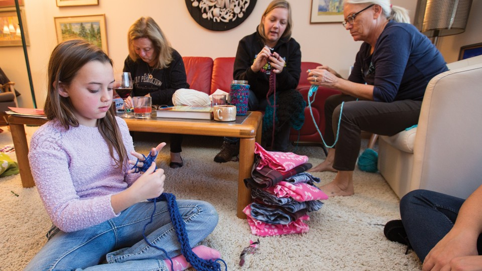 "Nylah Mossop (left) uses her fingers to knit a scarf during the launch of the ""Scarves for Kids"" project on Nov. 20. The event was organized by Jo Ann Emerson (right) and Sandra Williams (not pictured). Other participants included (left of Emerson) Amanda Gailey, associate professor of English, and Patsy Koch Johns."