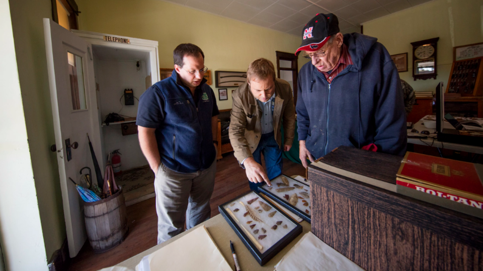 Dennis Kuhnel (from left) and Matt Douglass examine a collection brought in by John Furrow during an Oct. 7, 2016 Artifacts Roadshow in Mullen, Neb.