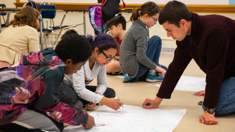 Worlds of Connections undergraduate mentor Luke Novak (right) works with a group of middle-school students to play a game demonstrating network science and the efficacy of vaccinations among community members.