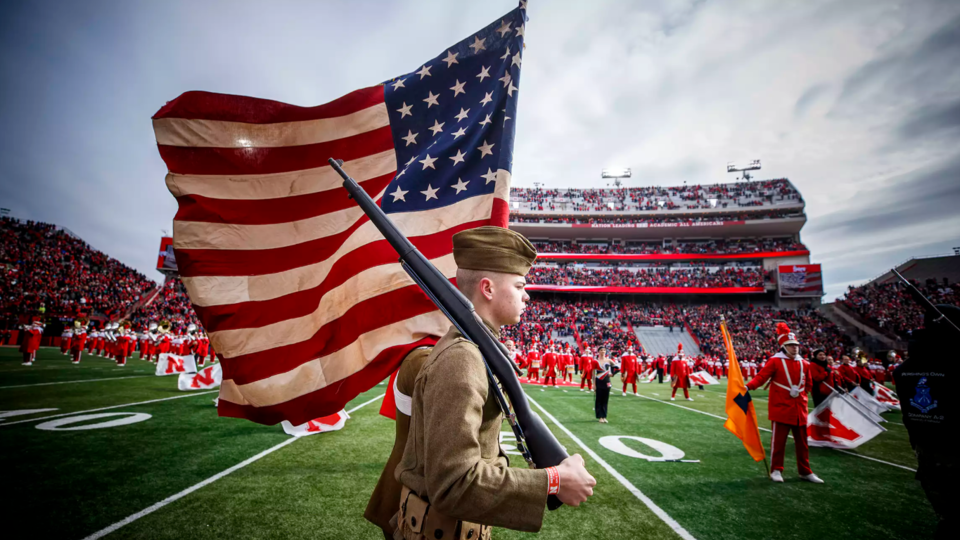 Members of the University of Nebraska–Lincoln ROTC color guard carry flags onto the field wearing authentic World War I uniforms as part of a Veterans Day observance in 2018. The Huskers will hold national anthem tryouts for the 2019-20 academic year on Aug. 14.