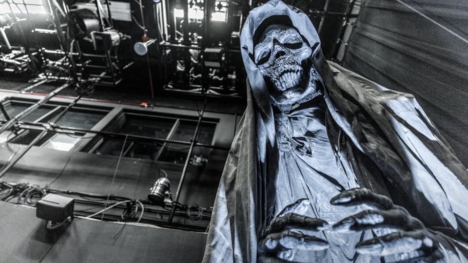 Large blue skeleton figure looming in haunted house