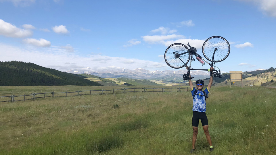 Nebraska's Chin Kiong Tee raises his bike for a photo in Wyoming's Bighorn National Forest. Tee's summer adventure featured a coast-to-coast bike ride in support of cancer victims.