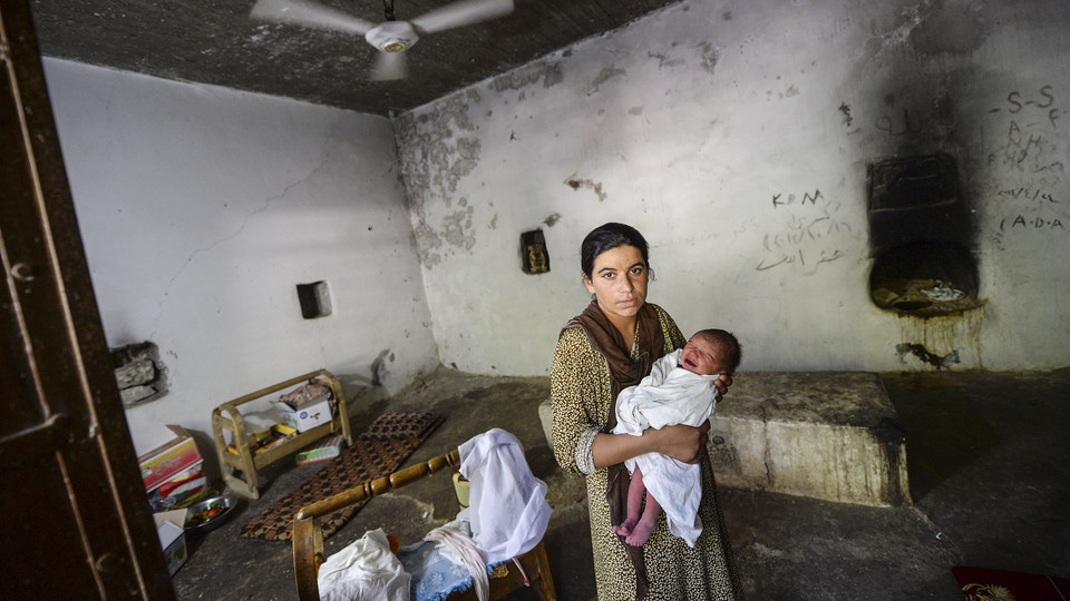 An unnamed Yazidi woman who escaped abuse from ISIS holds her baby in a refugee camp in Lalesh, Iraq.