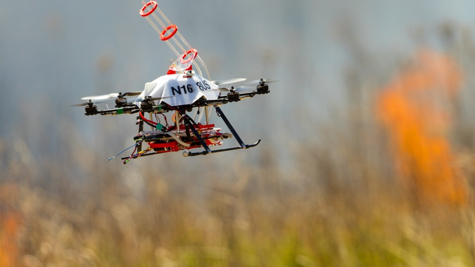 A UNL-designed drone returns to the side of a burn area for a reload of fireballs and the chemical to make them burn. The balls are carried aloft in the tubular structure atop the drone. The ball carries a chemical powder and, while airborne, the drone injects a second chemical. The drone then drops the ball and it bursts into flames within 60 seconds.