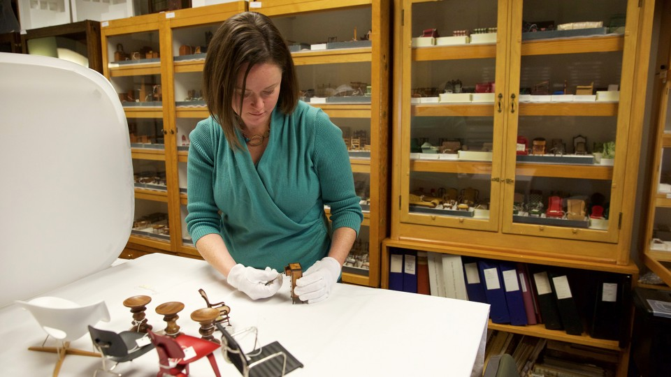 DiAnna Hemsath Collections Manager For UNLs Kruger Collection Examines A Miniature Piece Of Furniture