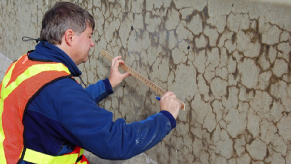 A worker measures cracks in a concrete median affected by alkali-silica reaction. A team led by UNL's Jinying Zhu has earned a federal grant to develop an online system to monitor and evaluate the health of concrete structures, including nuclear power plants.
