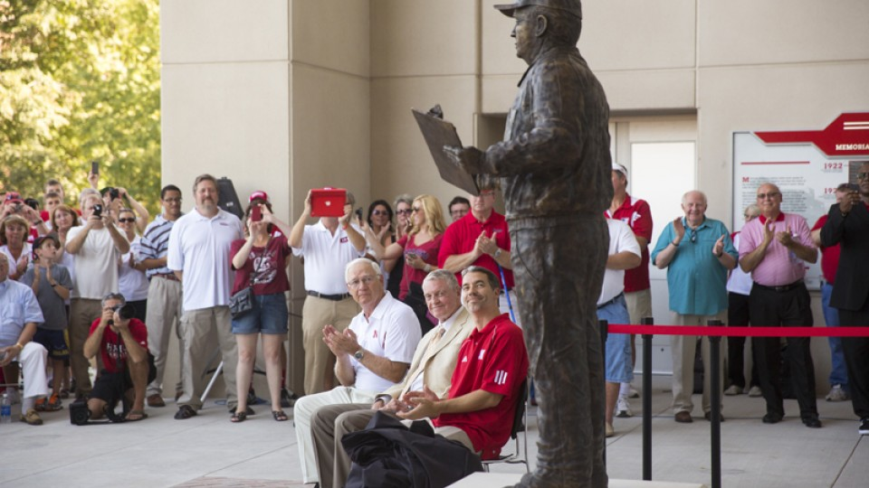 Mike Devaney, (Bob Devaney's son), Tom Osborne, the Cornhuskers' former head coach and athletic director, and Rob Devaney (Bob Devaney's grandson), look up at the just dedicated statue of Bob Devaney.  A commissioned statue of Hall-of-Fame football coach and former Cornhusker athletic director Bob Devaney was installed in the new East Memorial Stadium plaza Friday afternoon.