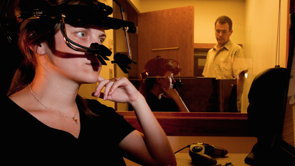 In this file photo, UNL psychology professor Michael Dodd (background) observes a study participant equipped with eyetrack technology.
