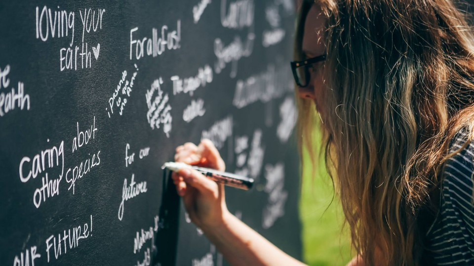 A student writes about what sustainability means to her on a Nebraska-shaped chalkboard during the university's 2016 Earth Day celebration in April.