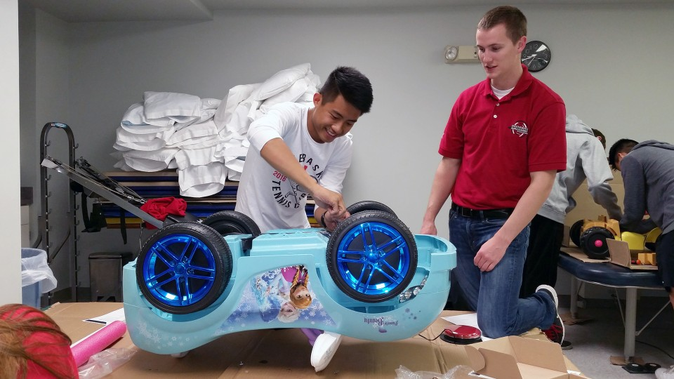 Two engineering students rewire an electric car during at the Go Baby Go build on Oct. 15.