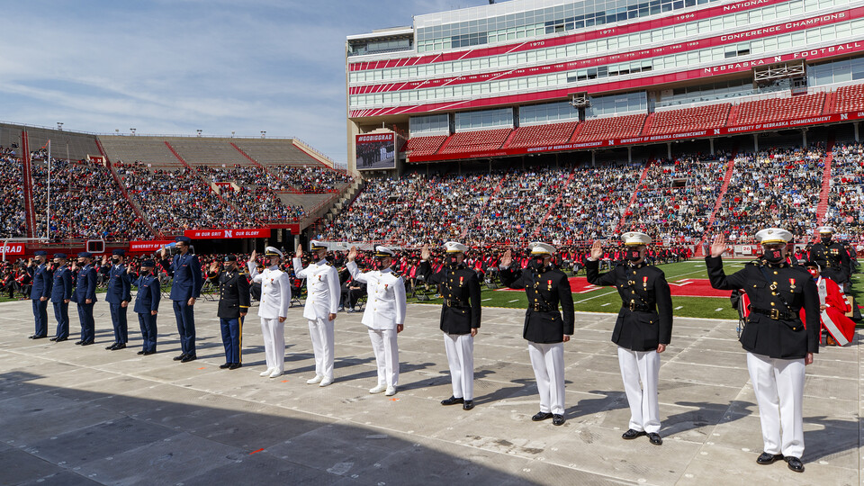 Air Force, Army and Naval ROTC members recite the oath of enlistment during the morning undergraduate commencement ceremony May 8 at Memorial Stadium. Some then changed into regalia to graduate with their colleges.