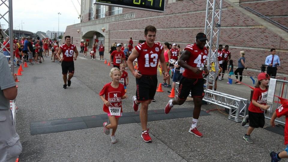Huskers run alongside participants outside of Memorial Stadium in the Nebraska Football Road Race.