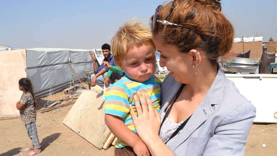 Vianne Sheikh consoles a toddler at a refugee camp in Iraq. The Husker is working to elevate stories of refugee women.