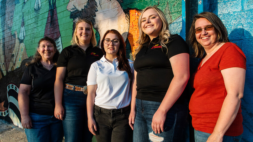 The three Rural Fellows and local partners pause in front of one of the downtown Chadron murals. Jenny Nixon (left), Chantelle Schulz, Hanna Jemison, Jacy Hafer and Kerri Rempp, tourism director for the Discover Northwest Nebraska.