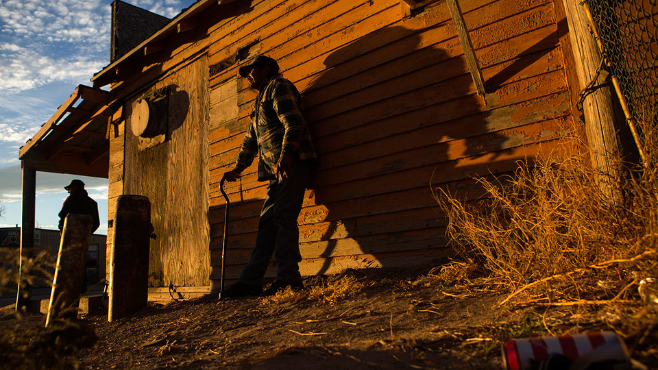 People stand beside a building as the sun sets over Whiteclay. Many of those who spend time drinking on the streets in Whiteclay spend their nights in a makeshift camp not far from the town.