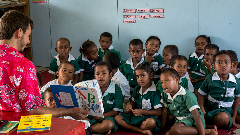 A Peace Corps worker reads to students in Fiji.