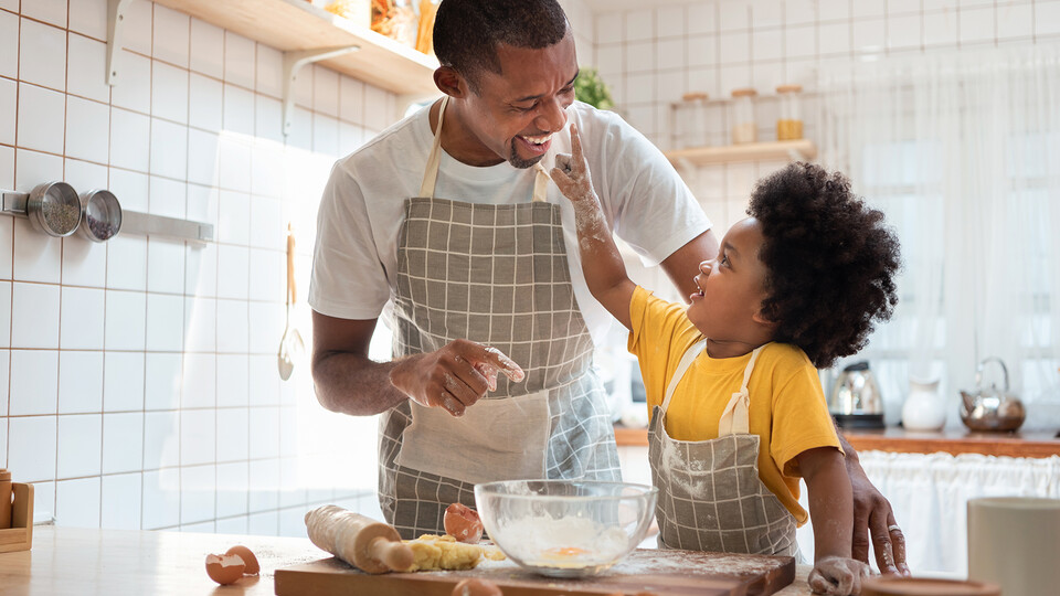 Dad and child baking together in a kitchen.