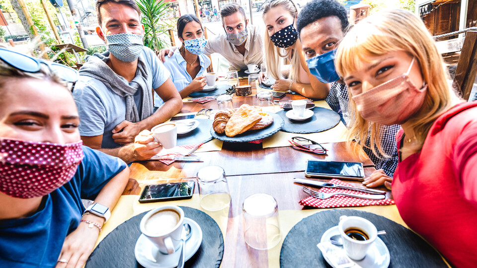 A group of friends meets up at a coffee house and takes a photo in masks.