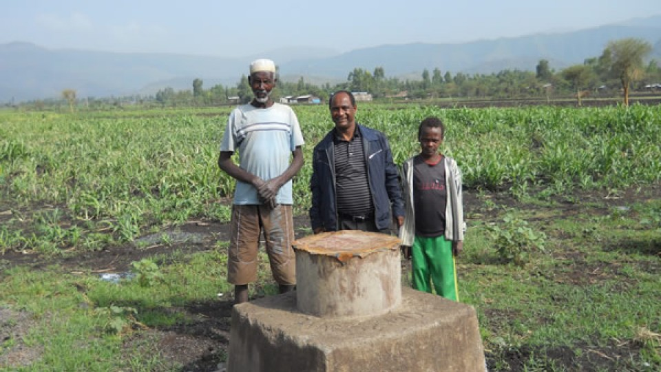 Tsegaye Tadesse, center, with a farmer and son at an irrigation demonstration site near Harbu, Ethiopia.