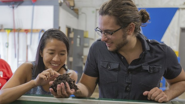 UNL students Vivian Nguyen (left) and Cale Brodersen examine worms that are turning food waste into compost at Big Red Worms, a new composting operation in west Lincoln. | Troy Fedderson, University Communications