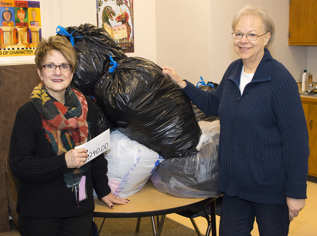 Linda Kern, Clinton Elementary faculty care coordinator, accepts the Coats for Clinton donations from Dee Ebbeka, SNR Community Engagement Committee member, on Dec. 9 at the school.   Shawna Richter-Ryerson, Natural Resources