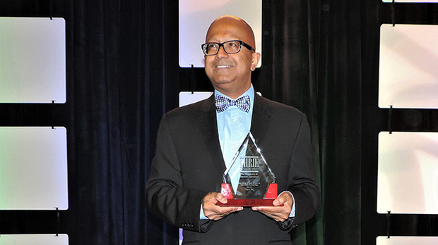 Dipra Jha grasps his ICHRIE award for innovation in teaching.