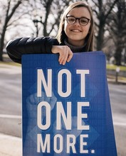 "Natalie Dettmer with her winning poster design, ""Not One More."" Photo by Adobe Project 1324."