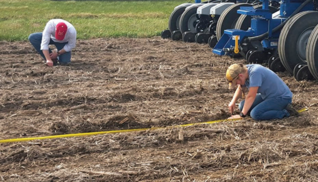 Joe Luck (left) and Rachel Stevens check seed placement of a multi-hybrid planter being tested as part of a collaborative research project being conducted by university researchers, industry and growers.